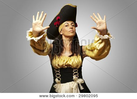 portrait of pirate woman gesturing stop against a grey background