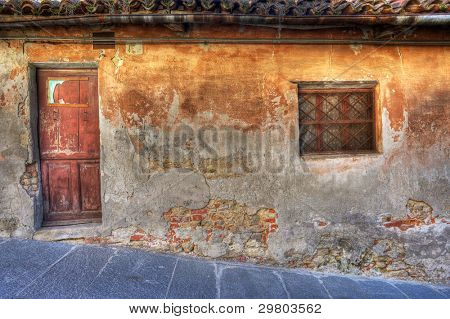 Old vintage abandoned house with small window and wooden door in town of La Morra, Northern Italy.