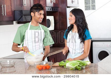 modern young indian couple cooking in kitchen