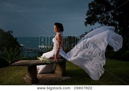 Bride Sitting With Dress Blowing In The Wind