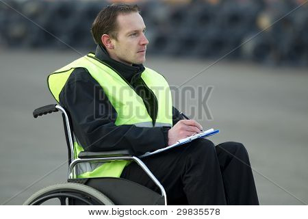 Supervisor Inspecting Wire Roll With Checklist On Wheelchair