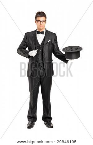 Full length portrait of a magician holding a magic wand and top hat isolated on white background