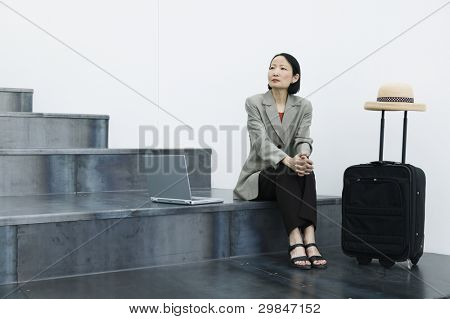 Businesswoman with laptop and luggage