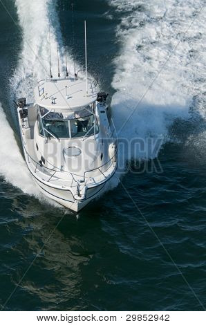 A speedboat moving through calm water in the Pacific Ocean.