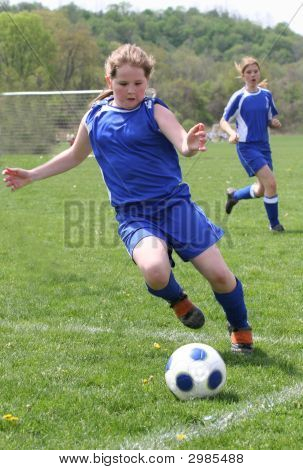 Teen Kicking Soccer Ball down the field