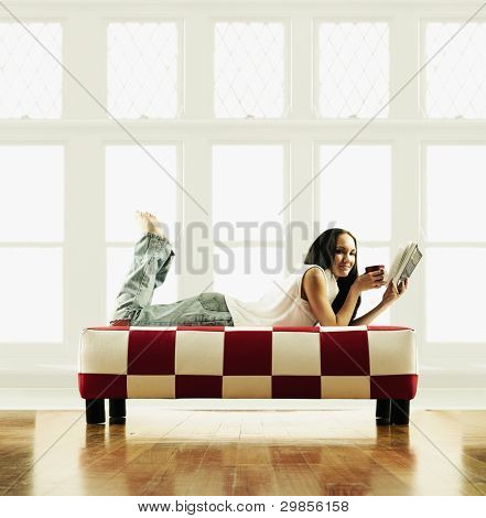 Young woman lying on a couch reading a book