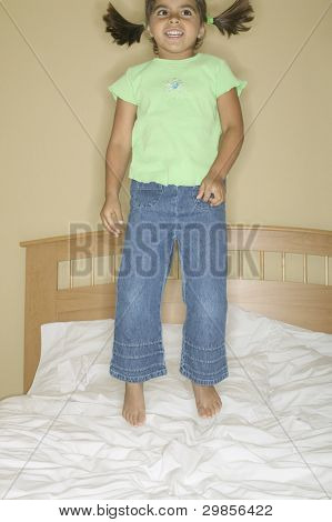 Young girl bouncing on a bed