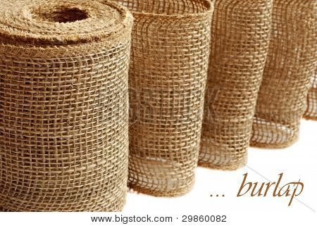 Burlap ribbon or garland (used for home decor and craft projects) on white background with copy space.  Macro with shallow dof.   Roughness concept  - could  be used to symbolize 'rough toilet paper'.