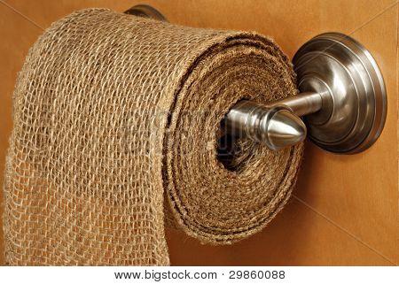 Humorística ainda vida de serapilheira rústica no distribuidor moderno papel higiênico com fundo de madeira.  Símbolo