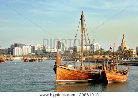 A jalibut dhow, with its distinctive vertical prow, tied up next to a smaller traditional boat - possibly a zaruq - in front of the landmark spiral mosque in Doha, Qatar