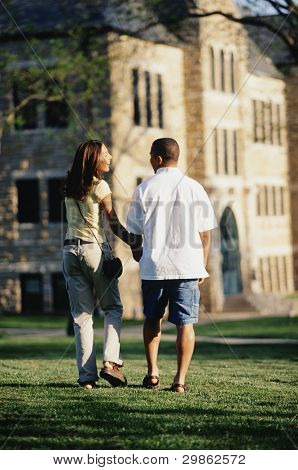 Rear view of couple walking across lawn