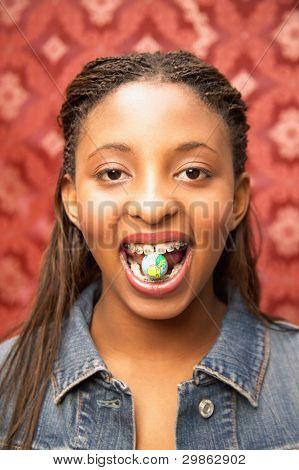 Portrait of teenage girl in braces with candy between teeth