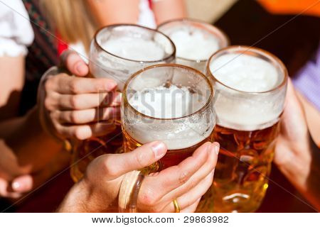 Four friends with a fresh beer in a Beer garden; close-up on beer stein