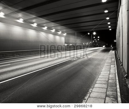 Tunnel road area at night with a smooth car lights trace.