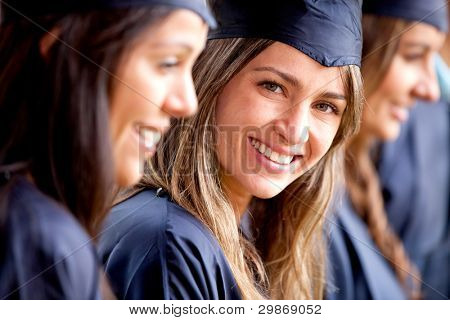 Beautiful female graduate standing out from a group of students
