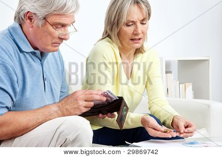 Senior couple with wallet counting Euro money on table at home
