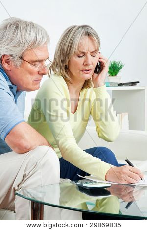Senior couple with paperwork calling phone hotline at home
