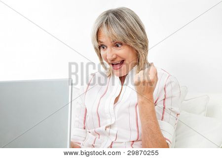 Happy senior woman cheering while looking at computer