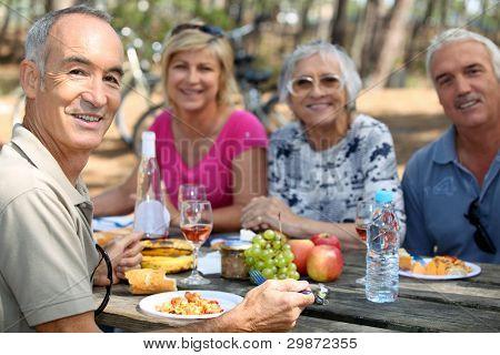 família comer piquenique na floresta