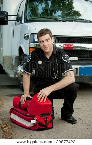 Portrait of a male paramedic in front of ambulance with portable oxygen unit