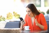Amazed Woman Checking Smart Phone Content Finding Good News In A Coffee Shop Terrace poster