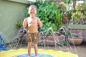 Cute Little Smiling Asian 2 - 3 Years Old Toddler Boy Child Having Fun Playing With Splash Water In  poster