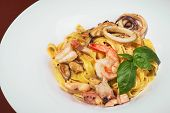 Pasta With Shrimps, Calamari, Fresh Parmesan Cheese On A Wooden Table, Terrace, Seafood, Fish Dish.  poster
