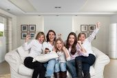 A group of  female family members sitting at home cheering