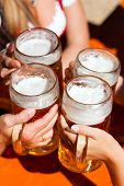 picture of stein  - Four friends with a fresh beer in a Beer garden - JPG