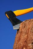 stock photo of disafforestation  - heavy ax put in stump against blue sky - JPG