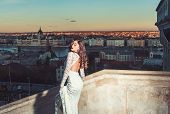 Sensual Woman With Long Hair On Balcony, Beauty. Woman In White Wedding Dress On Evening City View,  poster