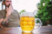 Mug Cold Fresh Beer On Table Close Up. Man Sit Cafe Terrace Enjoying Beer Defocused. Alcohol And Bar poster