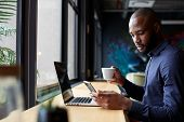 Mid adult black male creative sits by window having coffee, using a laptop and smartphone, side view poster