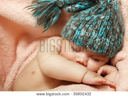 cute infant baby sleeping on pink plaid in funny hat, beautiful kid's face closeup with copyspace