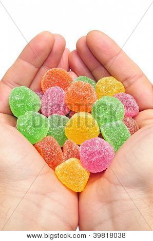 man hands full of gumdrops of different colors on a white background