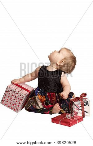 Baby In Patchwork Dress Holds Gifts And Looks Up