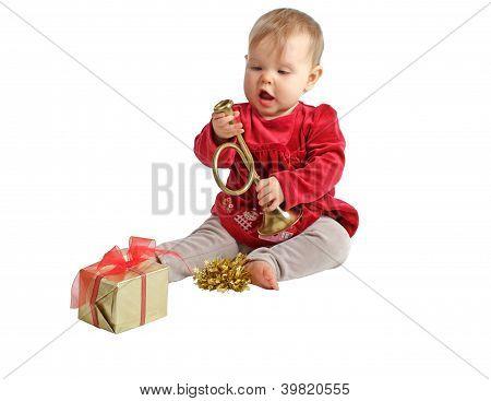 Baby Girl In Red Velvet Dress Inspects Toy Brass Horn