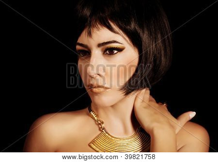 Photo of gorgeous woman with Cleopatra makeup, closeup portrait of beautiful female with stylish haircut isolated on black background, young lady wearing fashionable golden necklace, beauty salon
