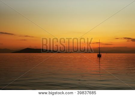Sunset over Angistri (on the left) and the mountains of the Peloponnese, in Greece, with a yacht moored nearby seen from Aegina