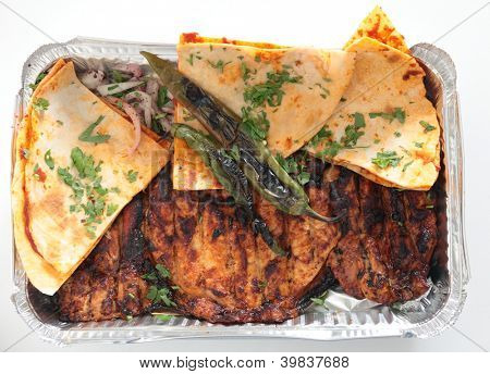A restaurant tray of Turkish or Arab spatchcocked, marinaded grilled chicken, served with flat Arab bread with a tomato topping, chopped onion, sumac and coriander salad and grilled chilli peppers.