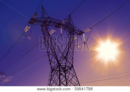 Electric high voltage post with sunset background