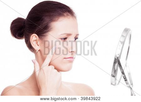 young woman having skin problems, looking into the mirror isolated against white background