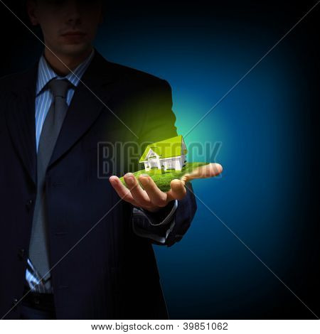 Residential building and a businessman holding it in his hands