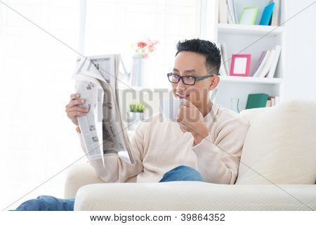 Southeast Asian male drinking coffee while reading news paper sitting on sofa at home, indoor lifestyle
