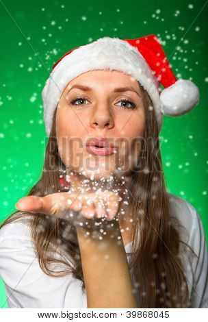 Girl In A Christmas Hat Blows Off Snowflakes