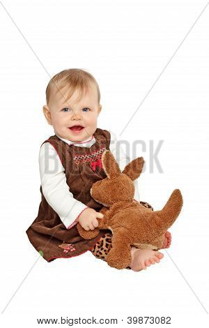 Happy Baby In Brown Velvet Dress Sits With Stuffed Toy