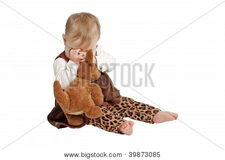 Cute Baby In Brown Velvet Dress Plays Peek-a-boo With Stuffed Toy