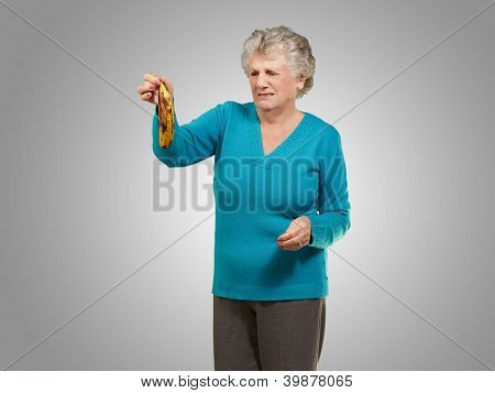 Senior woman holding a rotten banana over grey background