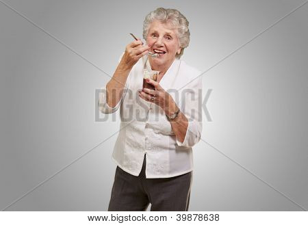 portrait of senior woman eating chocolate and cream cup over grey