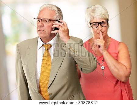 Man Taking On Cellphone In Front Of Woman Gesturing, Indoor